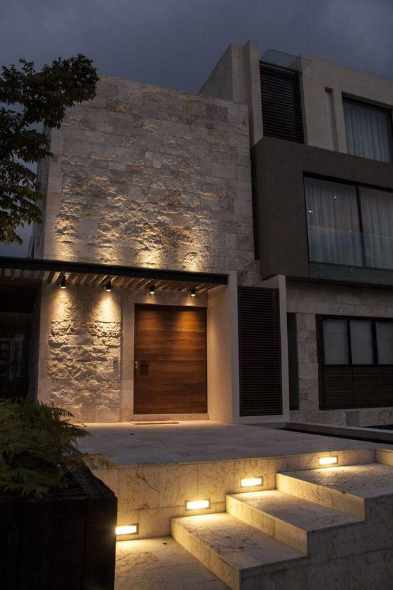 fachada de la casa con pared de piedra